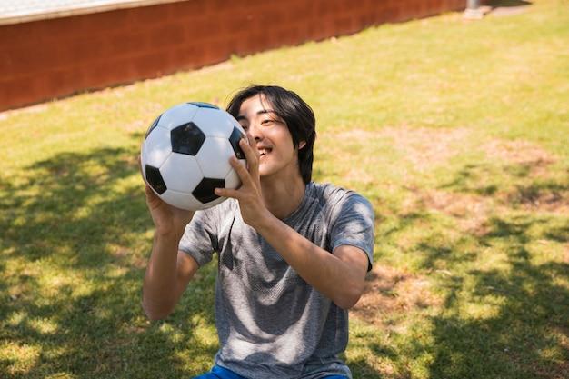 Веселый подросток азиатский студент ловит футбольный мяч Бесплатные Фотографии