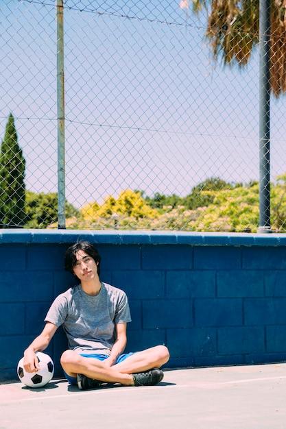 Азиатский подросток студент сидит возле забора спортплощадки Бесплатные Фотографии