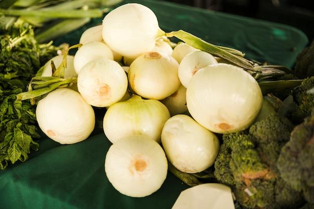 市場でテーブルの上の緑の野菜と健康的な白ねぎ 無料写真