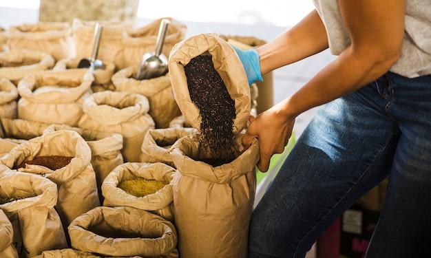 黒米を食料品店で茶色の紙袋に入れている男 無料写真