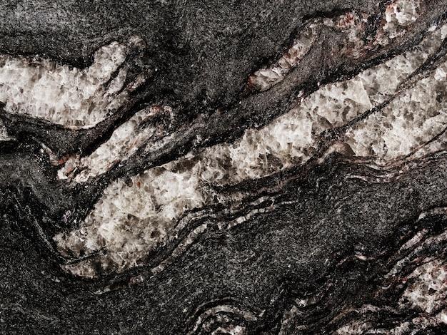 黒い岩の背景にテクスチャの白いラフ 無料写真
