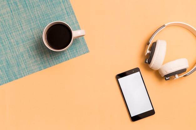 スマートフォンとオレンジ色の背景上のカップ付きヘッドフォン 無料写真