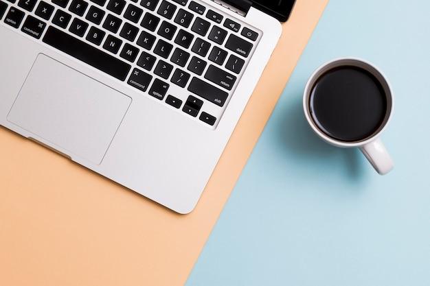 Ноутбук и чашка кофе на фоне красочных Бесплатные Фотографии