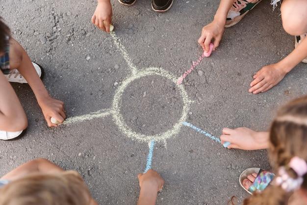 チョークで太陽を描く子供たち 無料写真