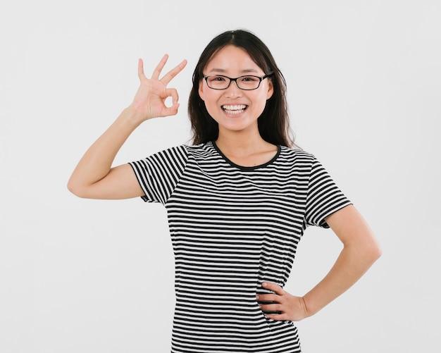 Женщина в очках, давая знак ок Бесплатные Фотографии