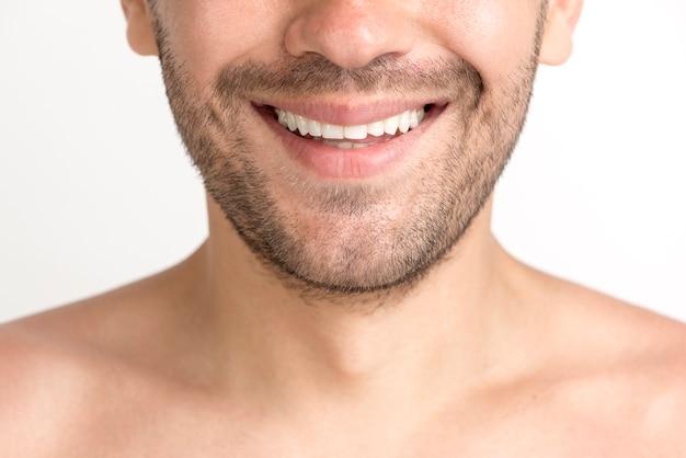 歯を見せる笑顔で無精ひげの若い男のクローズアップ 無料写真