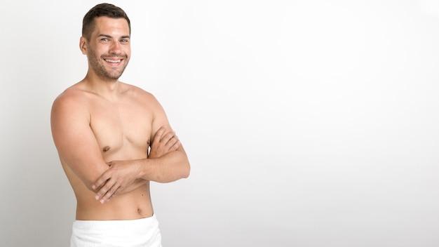 Молодой человек без рубашки, стоя со скрещенными руками Бесплатные Фотографии