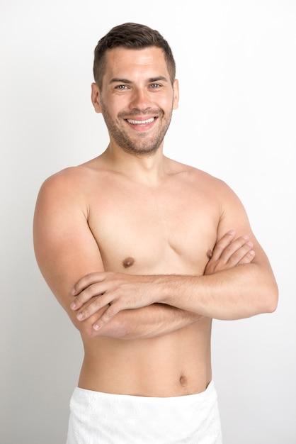 Улыбающийся молодой человек со скрещенными руками, глядя на камеру Бесплатные Фотографии