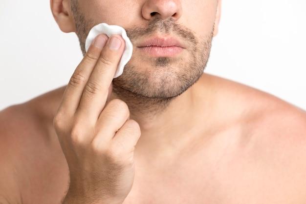 綿パッドで顔を洗浄する男のクローズアップ 無料写真