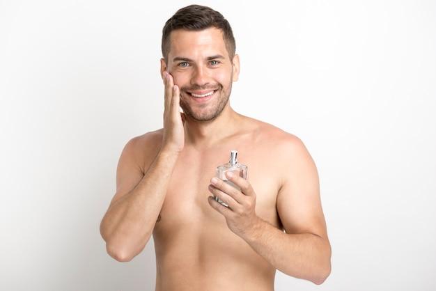 アフターシェーブローションボトルを押しながら頬に触れる笑みを浮かべて男 無料写真