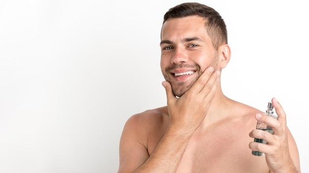 白い背景に対して立っているアフターシェーブローションを噴霧幸せな男 無料写真
