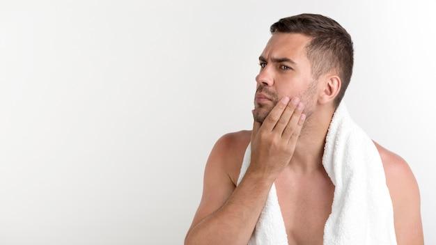 Человек без рубашки с полотенцем на шее проверяет лицо на белом фоне Бесплатные Фотографии
