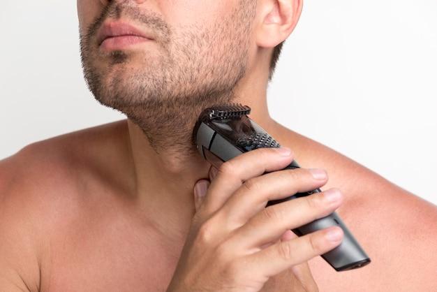 Портрет молодого человека, брить бороду с электробритвы Бесплатные Фотографии