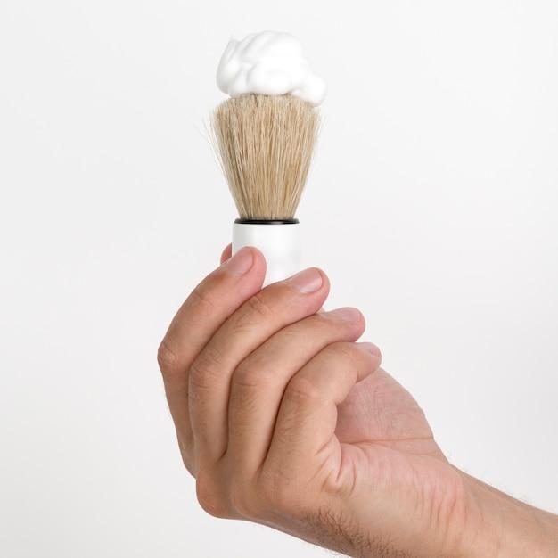 白い壁にシェービングブラシと泡を持っている人間の手のクローズアップ 無料写真