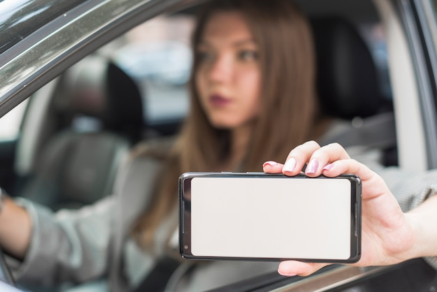 ビジネスの女性が車の中でスマートフォンを表示 無料写真
