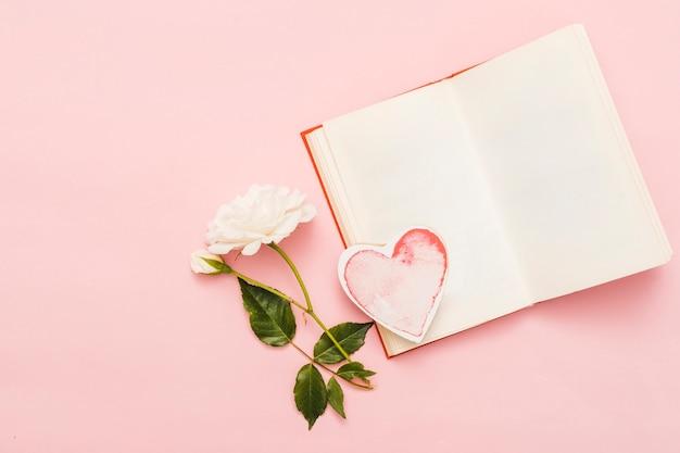Вид сверху книги с карточкой в форме сердца Бесплатные Фотографии