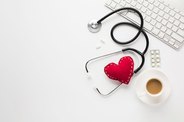 Стетоскоп с красным сердцем возле лекарств; чашка кофе и клавиатура на белом столе Бесплатные Фотографии