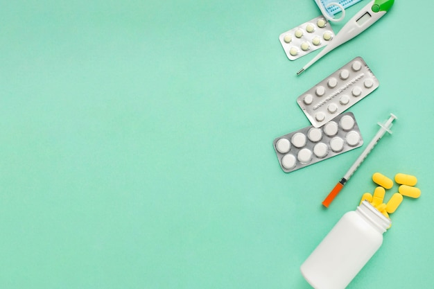 Таблетки и медицинские инструменты на зеленой поверхности с пространством для текста Бесплатные Фотографии