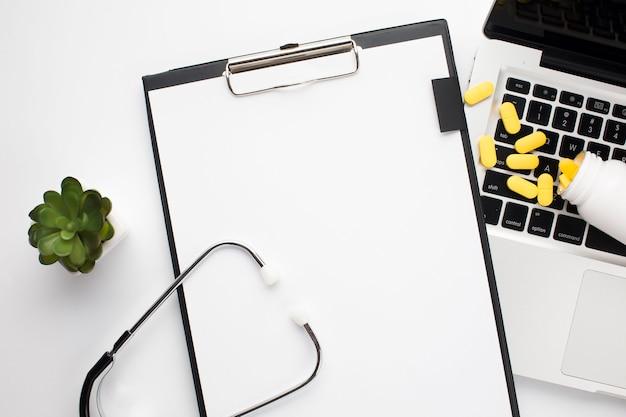 机の上のラップトップと聴診器にこぼれる丸薬の近くのホワイトペーパーとクリップボード 無料写真