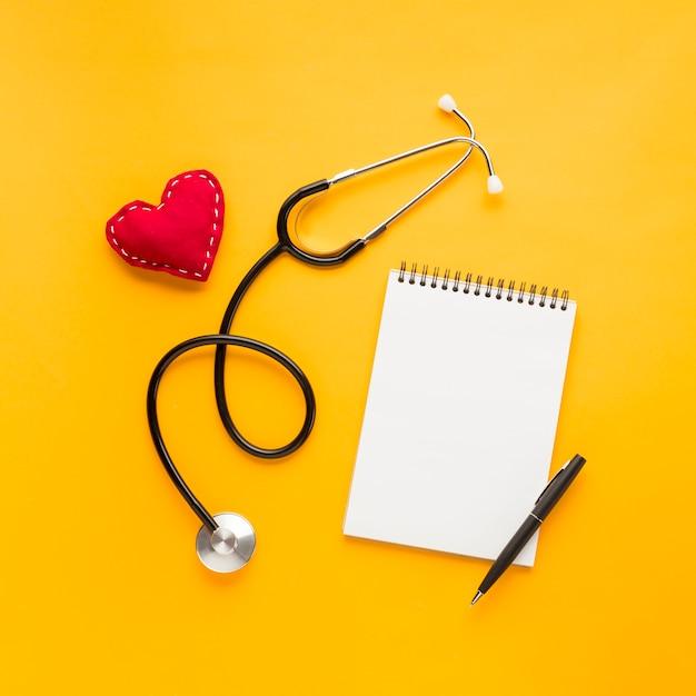 ペンで空白のスパイラルメモ帳。ステッチされたハート形;明るい黄色の背景の上の聴診器 無料写真