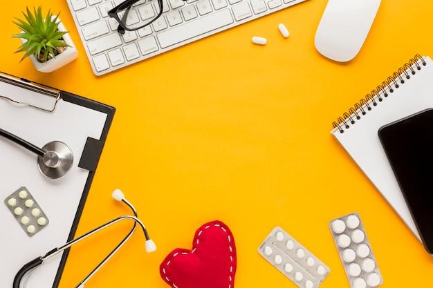 スパイラルメモ帳の平面図。携帯電話;ブリスターパック錠;聴診器;クリップボードと黄色の机の上の多肉植物 無料写真