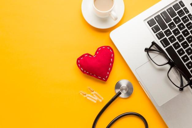 ノートパソコンのキーボードのクローズアップ。ステッチ布のおもちゃ;コーヒーカップ;アンプル;黄色の机に対して聴診器 無料写真