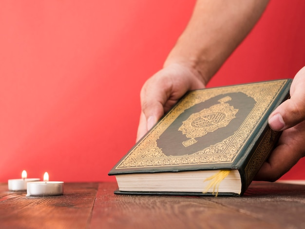 コーランを拾う手を閉じる 無料写真