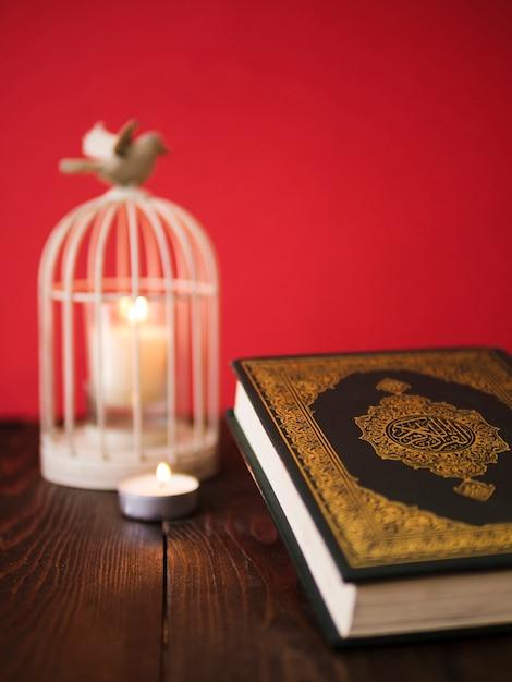ビンテージバードケージキャンドルホルダー付きテーブルの上のコーラン 無料写真