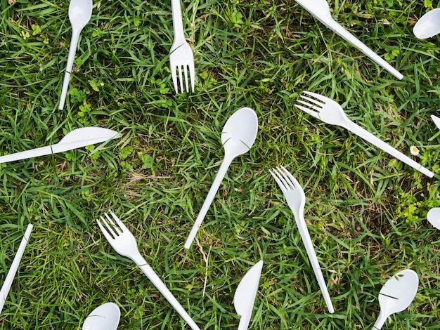 公園で緑の芝生の上の白いプラスチック製カトラリー 無料写真