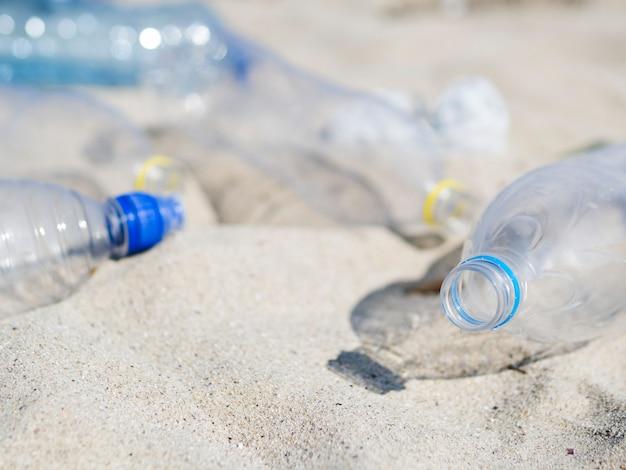 砂の上の空の廃プラスチックウォーターボトルのクローズアップ 無料写真