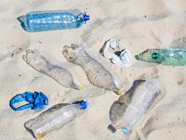Пустые пластиковые бутылки с водой и полиэтиленовый пакет на песке Бесплатные Фотографии