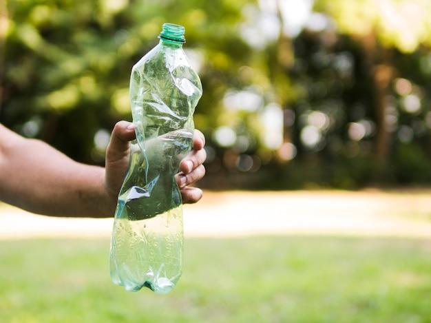 人間の手持ち株屋外で砕いたペットボトル 無料写真