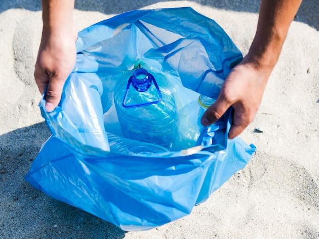 Высокий угол зрения руки, держа синий мешок для мусора на песке Бесплатные Фотографии