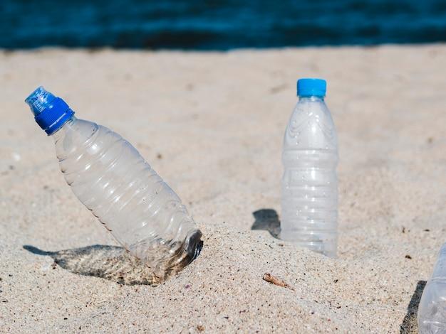 ビーチで砂の上の空のペットボトル 無料写真