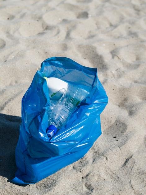 ビーチで砂の上のプラスチック製のゴミの青い袋 無料写真