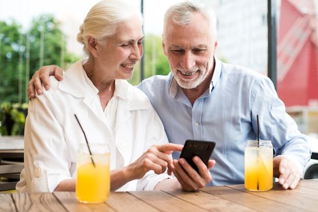 ミディアムショット老人、携帯電話を見て 無料写真