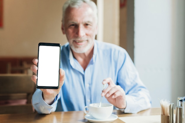 Средний выстрел старика, держащего смартфон Бесплатные Фотографии