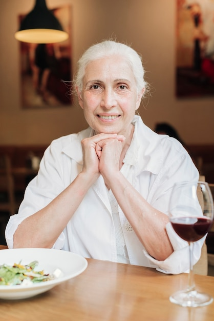 正面の老婦人がレストランでポーズ 無料写真