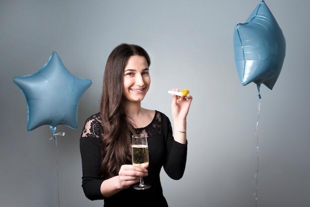 ガラスとパーティーホーンを持つ陽気な若い女性 無料写真