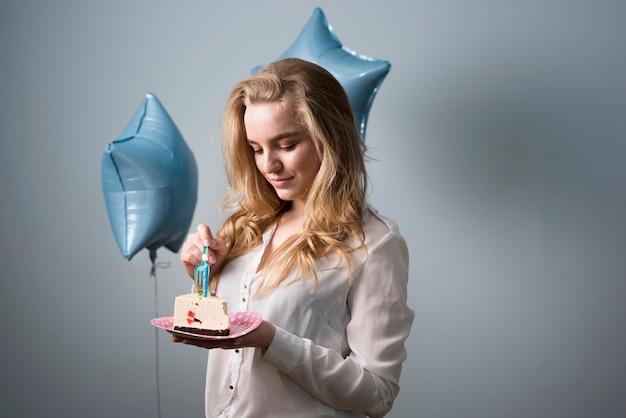 うれしそうな若い女性の誕生日ケーキを食べる 無料写真