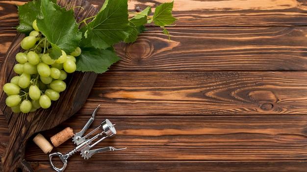 木製の背景にコルク栓抜きとブドウの房 無料写真