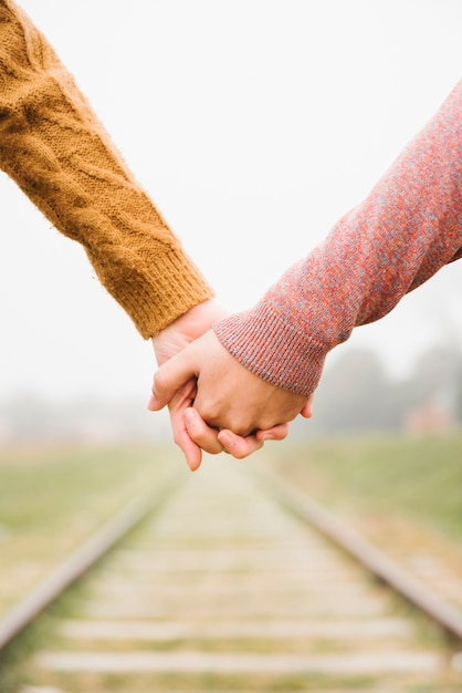 手を取り合って立っている素敵な若いカップル 無料写真