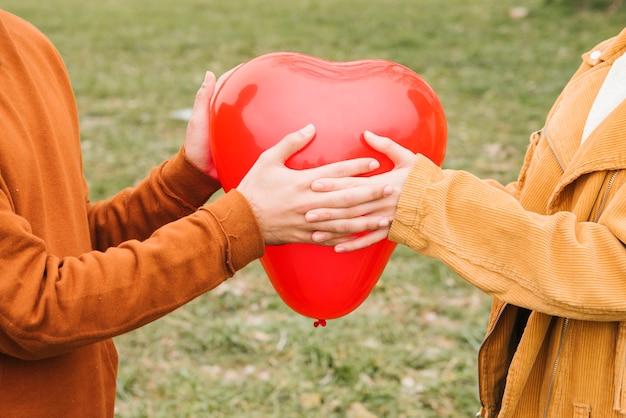 ハート形の風船を持って幸せな若いカップル 無料写真
