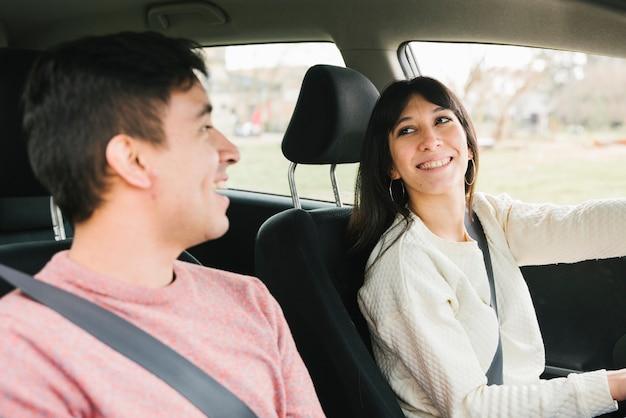 Улыбающаяся молодая пара едет на автомобиле Бесплатные Фотографии