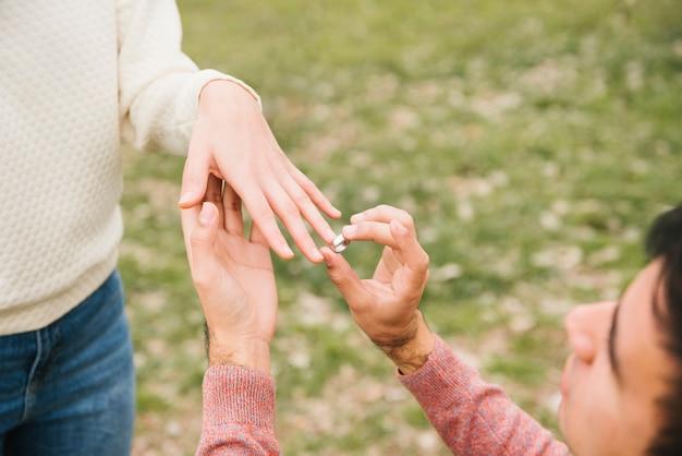 Молодой человек ставит обручальное кольцо на палец любимой Бесплатные Фотографии