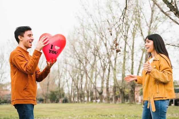 屋外バルーンを引く幸せなカップルを愛する 無料写真