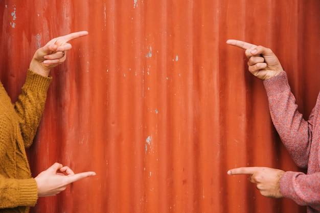 オレンジ色の金属製の壁を指して作物の手 無料写真