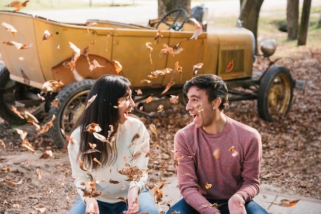 秋の葉を投げ、お互いを見て喜んでいるカップル 無料写真
