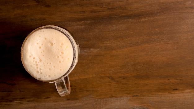 木製のテーブルの上の泡ビールのグラス 無料写真