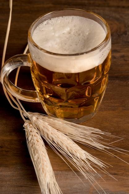 木製テーブルの上のスパイク大麦と新鮮なビールの水差し 無料写真